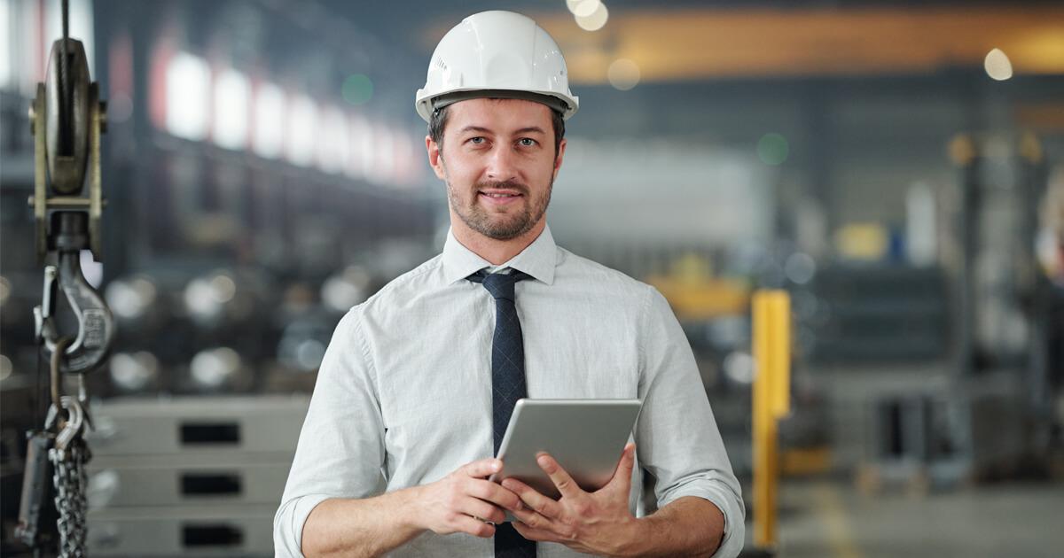 Home com capacete de segurança segurando tablet