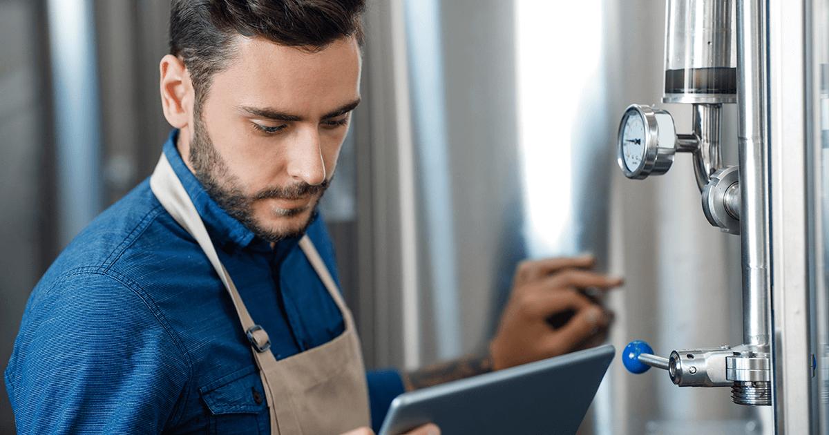Retrato do trabalhador da cervejaria verificando o processo de fermentação, tecnologia e aplicativo para pequenas empresas